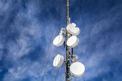 Les antennes sur le réseau mobile dominent sur un ciel bleu Système global pour des communications mobiles Photo stock