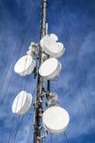 Les antennes sur le réseau mobile dominent sur un ciel bleu Système global pour des communications mobiles Image stock