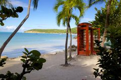Les Antilles, les Caraïbe, l'Antigua, le St Georges, la baie de Dickenson, la plage et la cabine téléphonique rouge Photographie stock libre de droits