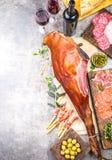Les apéritifs ajournent avec le serrano entier ibérien espagnol de jamon de jambon, les casse-croûte, les olives et le vin rouge  Images libres de droits