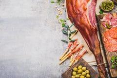 Les apéritifs ajournent avec le serrano entier ibérien espagnol de jamon de jambon, les casse-croûte, les olives et le vin rouge  Photo stock