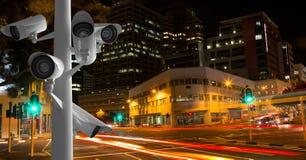 Les appareils-photo de télévision en circuit fermé contre la lumière traîne dans la ville la nuit images stock