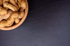 Les arachides se situent dans une tasse en bois sur un conseil en pierre noir sous forme de cadre, l'espace pour le texte Photo stock