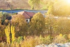 Les arbres d'automne et la maison de campagne colorés, le soleil rayonne Image libre de droits
