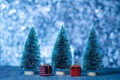 Les arbres de Noël avec des boîte-cadeau et le bokeh s'allument sur la table en bois Photos libres de droits