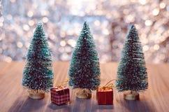 Les arbres de Noël avec des boîte-cadeau et le bokeh s'allument sur la table en bois Images libres de droits