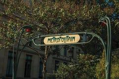 Les arbres feuillus et le Nouveau dénomment la voûte où on lui écrit le ` métropolitain de ` dans l'entrée de souterrain à Paris photographie stock