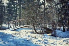 Les arbres givrés d'hiver et le vieux pont neigeux pendant l'hiver se garent Image libre de droits