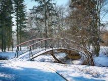 Les arbres givrés d'hiver et le vieux pont neigeux pendant l'hiver se garent Images stock