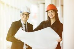 Les architectes d'homme d'affaires regardent l'architecte de papier de femme d'affaires de plan dans le bureau pour discuter des  image stock