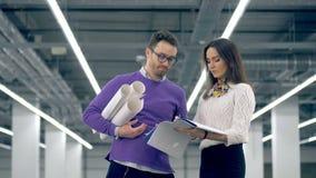Les architectes discutent un plan, tenant les rouleaux de papier dans des mains dans l'intérieur énorme de bureau clips vidéos