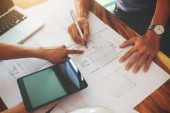 Les architectes machinent la discussion à la table avec le modèle - clo Photographie stock