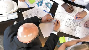 Les architectes multiraciaux et les concepteurs discutent de nouveaux projets Vue supérieure banque de vidéos