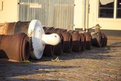 Les armes à feu rouillées se situent dans un vieux port au sol Photos stock