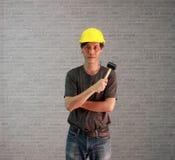 Les articles d'homme de technicien jaunissent le casque avec les jeans gris-foncé de T-shirt et de denim tenant et étreignant le  photo libre de droits