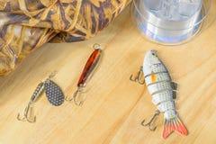 Les articles de pêche et la pêche leurrent sur le fond des planches en bois Images libres de droits