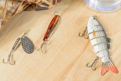 Les articles de pêche et la pêche leurrent sur le fond des planches en bois Images stock