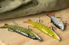 Les articles de pêche et la pêche leurrent sur le fond des planches en bois Image stock