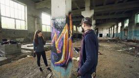 Les artistes de graffiti des jeunes emploient la peinture d'aérosol pour décorer le bâtiment industriel abandonné avec le graffit banque de vidéos