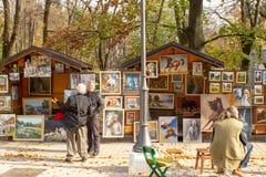 Les artistes de rue vendent des peintures aux touristes sur le marché en plein air image stock