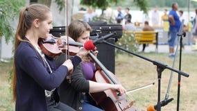 Les artistes exécutent la composition musicale sur le violoncelle et le violon pour des passants, filles jouent sur des instrumen clips vidéos
