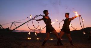 Les artistes professionnels montrent une exposition du feu à un festival d'été sur le sable dans le mouvement lent Quatrièmes acr clips vidéos