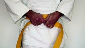 Les arts martiaux vêtx, gi de judo - l'homme tendent sa ceinture jaune sur un kimono blanc banque de vidéos