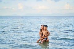 Les Asiatiques de maman et de fils se baignent en mer images stock