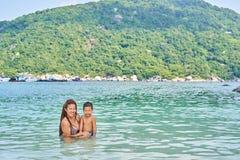 Les Asiatiques de maman et de fils se baignent en mer photo stock