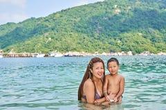 Les Asiatiques de maman et de fils se baignent en mer photos stock