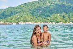 Les Asiatiques de maman et de fils se baignent en mer images libres de droits