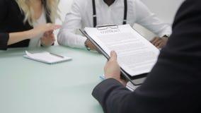 Les associés multi-ethniques discutent le contrat dans le bureau banque de vidéos