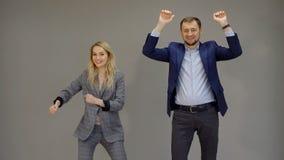 Les associés sont danse, marquant une affaire réussie sur le fond gris d'isolement photos libres de droits