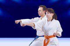 Les athlètes adultes de bras de poinçon battent dans le karategi Image libre de droits