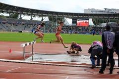 Les athlètes CONCURRENCENT sur les 3000 mètres de clocher Photo stock