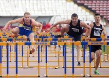 Les athlètes d'hommes concurrencent dans des obstacles de 110 m Photo stock