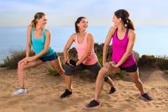 Les athlètes de conversation occasionnelle s'étirant dans l'exercice classent dehors avant essai et hausse sur le chemin de traîn Image libre de droits