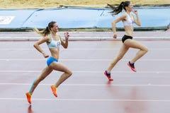 Les athlètes de fille courent 400 mètres sous la pluie Images stock