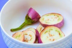 Les aubergines de brinjal découpent des morceaux en tranches sur le backg bleu d'isolement par tasse blanche photographie stock