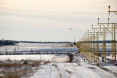 Les avions décollent de la piste avec le système d'éclairage dans le premier plan Images stock