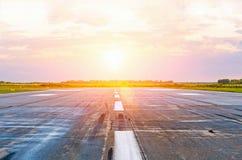 Les avions de piste d'aéroport avec des traces des pneus en caoutchouc à l'aube pendant le matin avec le soleil brillent Image stock