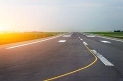 Les avions de piste d'aéroport avec des traces des pneus en caoutchouc à l'aube pendant le matin avec le soleil brillent Images stock