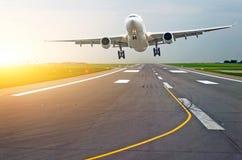 Les avions de piste d'aéroport avec des traces des pneus en caoutchouc à l'aube pendant le matin avec le soleil brillent Images libres de droits