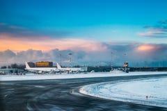 Les avions se tiennent sur le terminal d'aéroport international dans le début de la matinée Images stock