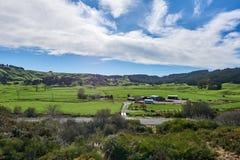 Les bâtiments de grange sur l'herbe ont couvert des prés Photographie stock