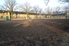Les bâtiments des écuries et d'une arène ouverte du cheval-élevage centrent Image stock