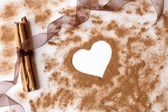Les bâtons de cannelle avec le ruban et la cannelle d'organza saupoudrent en forme de coeur Images libres de droits