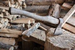 Les bâtons de hache dans le rondin Image stock