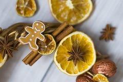 Les bâtons de la cannelle, fleurs de badian ou anis, ont séché des oranges et des citrons et des bonhommes en pain d'épice Photo stock