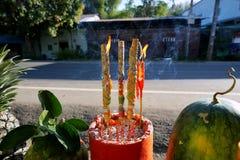 Les bâtons et la lueur d'une bougie d'encens brûlent dans le pot d'encens avec le soleil photo stock